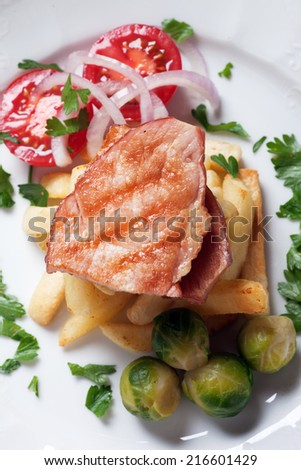 Grilled ham slices with brussel sprout and french fries