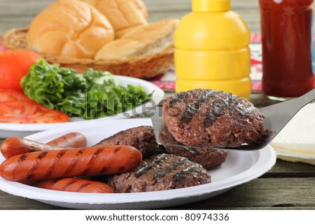 Grilled hamburgers, with one on a spatula, and hot dogs on a picnic table - stock photo