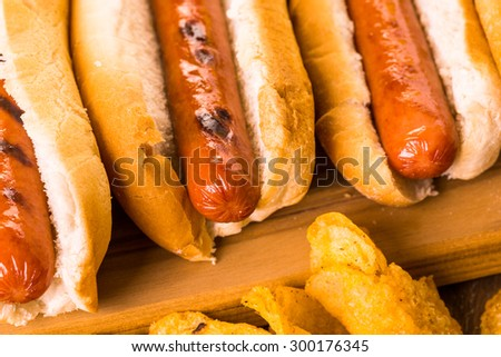 Grilled hot dogs on a white hot dog buns with chips and baked beans on the side.
