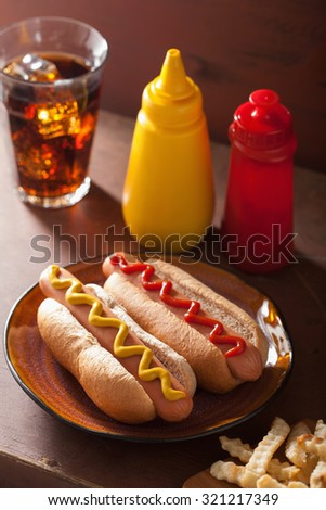 grilled hot dogs with mustard ketchup and french fries - stock photo