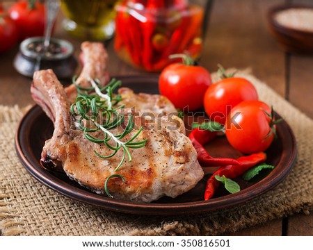 Grilled juicy steak on the bone with vegetables on a wooden background. - stock photo