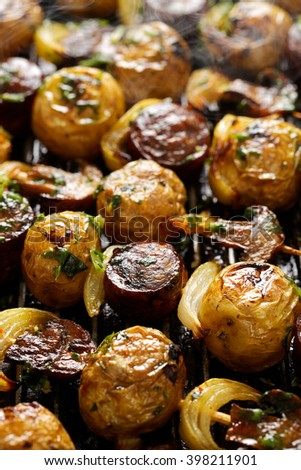 Grilled kebabs with potatoes, sausage, mushrooms and onions  - stock photo