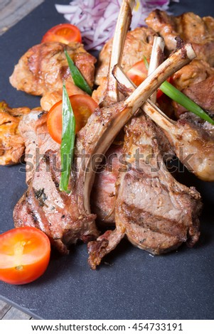 Grilled lamb meat with tomatoes and herbs