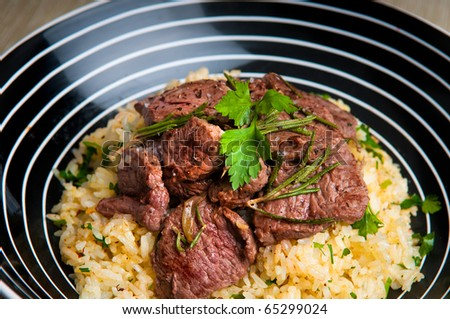 Grilled lamb on saffron rice - stock photo