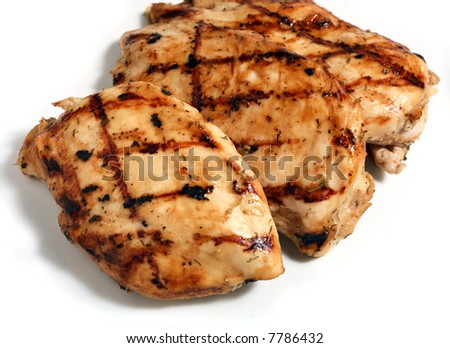 Grilled marinaded and herbed chicken breasts on a white plate. - stock photo