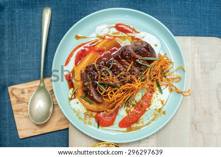 Grilled meat and carrots in a tomato sauce. Mediterranean meat dishes. Meat on a plate lying on a wooden tray. - stock photo