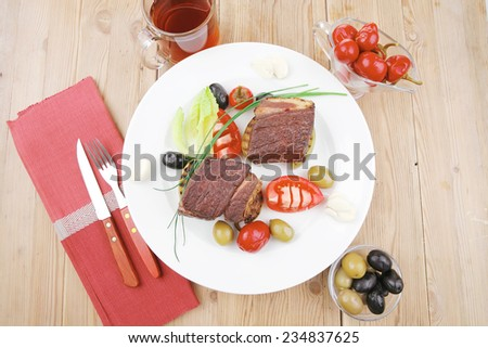 grilled meat : beef ( lamb ) garnished with tomatoes , green and black olives, tomatoes and juice on wooden table - stock photo