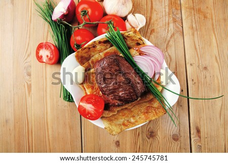 grilled meat : beef ( pork ) garnished with tomatoes salad in bowl , green chives , and tomatoes on side on wooden table - stock photo
