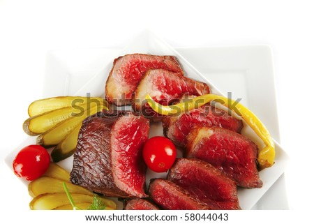 grilled meat chunk and slices on white plates - stock photo