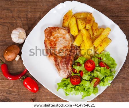 grilled meat fillet steak with fried potato and vegetables salad in a plate on wooden table - stock photo