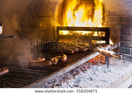 Grilled meat in barbecue with flames and coals.