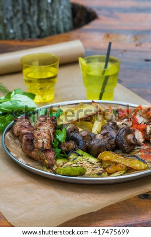 Grilled meat, mushrooms and vegetables (paprika, potatoes, zucchini) served on big plate with herbs and lemonade - stock photo