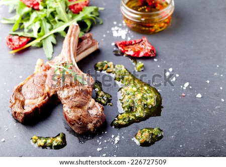 Grilled meat, mutton, lamb rack with fresh salad and sauce on black stone plate. Copy space  - stock photo