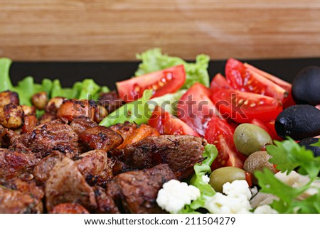 grilled meat on a plate served with vegetables - stock photo