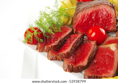 grilled meat on white plates with peppers and tomato - stock photo