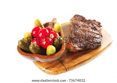 grilled meat on wooden plate with salty vegetables - stock photo
