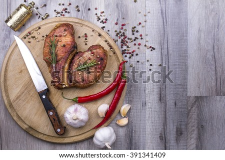 Grilled meat (pork) steaks on cutting board with hot peppers, garlic and knife, peppers mix, and rosemary on wooden cutting board with space for text. - stock photo