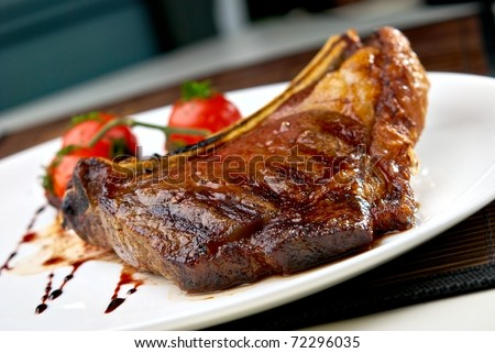 Grilled meat ribs on white plate with tomatoes chives and dark hot sauce - stock photo
