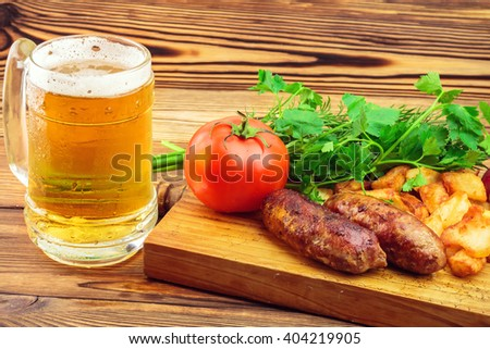 Grilled meat sausages with fried potatoes, fresh produce and mug of beer on wooden board. - stock photo