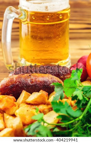 Grilled meat sausages with fried potatoes, fresh produce and mug of beer on wooden board, selective focus - stock photo