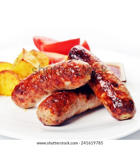 grilled meat sausages with potatoes and tomatoes - stock photo
