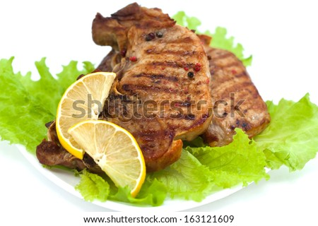 Grilled meat steak with green salad and lemon, isolated on white background - stock photo