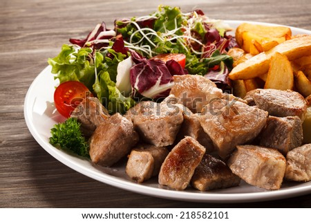 Grilled meat with baked potatoes and vegetables - stock photo