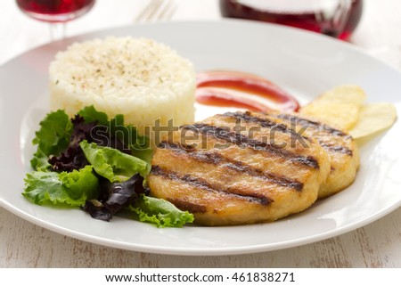 grilled meat with boiled rice and salad on white dish