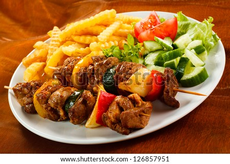 Grilled meat with French fries and vegetable salad - stock photo