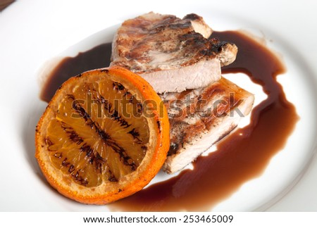 Grilled meat with orange sauce on a white plate. - stock photo