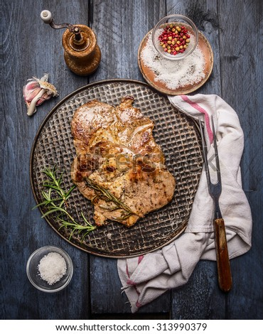grilled meat with spices on an iron baking tray with a napkin and fork on a rustic wooden background, top view - stock photo