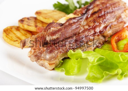 Grilled meat with vegetables on white plate