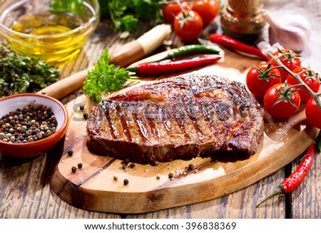 grilled meat with vegetables on wooden board - stock photo