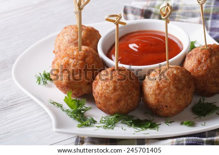 Grilled meatballs on skewers and ketchup on a plate close-up, horizontal  - stock photo