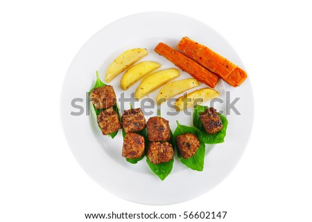 grilled meatballs on white plate with basil and potatoes