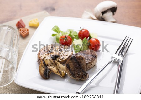 grilled meats and vegetables on plate served and decorated - stock photo