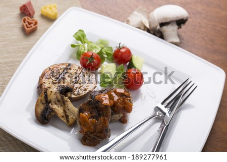 grilled meats and vegetables with sauce on plate served and decorated