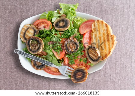 Grilled mushroom salad with fresh frilly lettuce and tomato served with toasted bread for a healthy lunchtime snack, viewed from above on a beige textile - stock photo