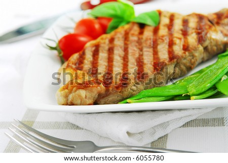 Grilled New York beef steak served on a plate with vegetables