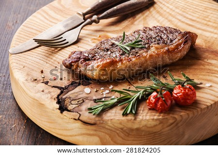 Grilled New York Striploin Steak with salt and pepper on meat cutting board on dark wooden background - stock photo
