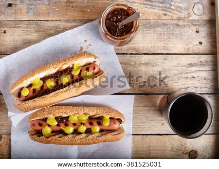 Grilled New York style Hot Dog with onion sauce, mustard and kethcup. Glass of Cola on back on wood background - stock photo