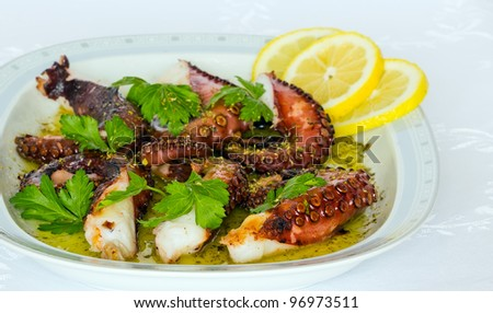 Grilled octopus with olive oil, lemon, oregano and parsley - stock photo