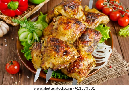 Grilled of chicken thighs on skewers with vegetables - stock photo