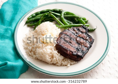 grilled organic pork chop with rice and green beans, from an ethical local farm - stock photo