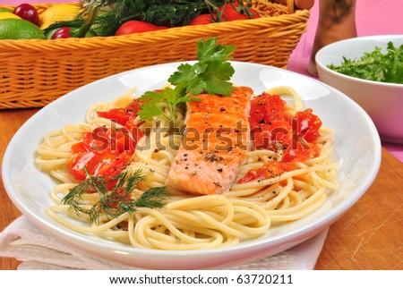 grilled organic salmon on some tomato spaghetti - stock photo