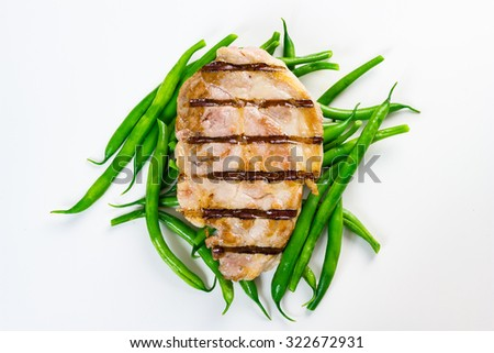 Grilled piece of pork on green beans, isolated on white background. - stock photo