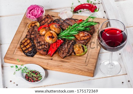 Grilled pieces of meat and different vegetables on wooden board - stock photo