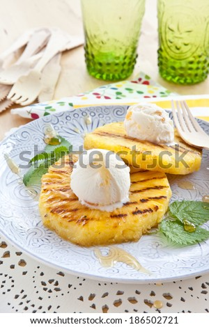 Grilled pineapple with scoops of vanilla ice cream - stock photo