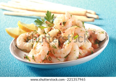 Grilled pink shelled marine prawns seasoned with olive oil and herbs served with lemon and bread sticks for a tasty seafood starter to dinner, on turquoise blue