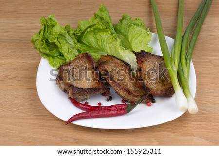 Grilled pork chop on a plate with onions and peppers lettuce